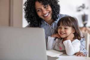 Mother & Daughter smiling and looking at a laptop