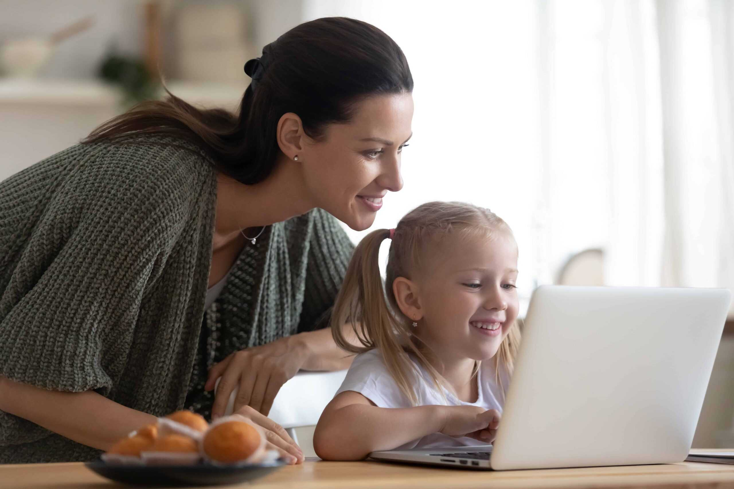 Mom & Daughter smiling looking at laptop
