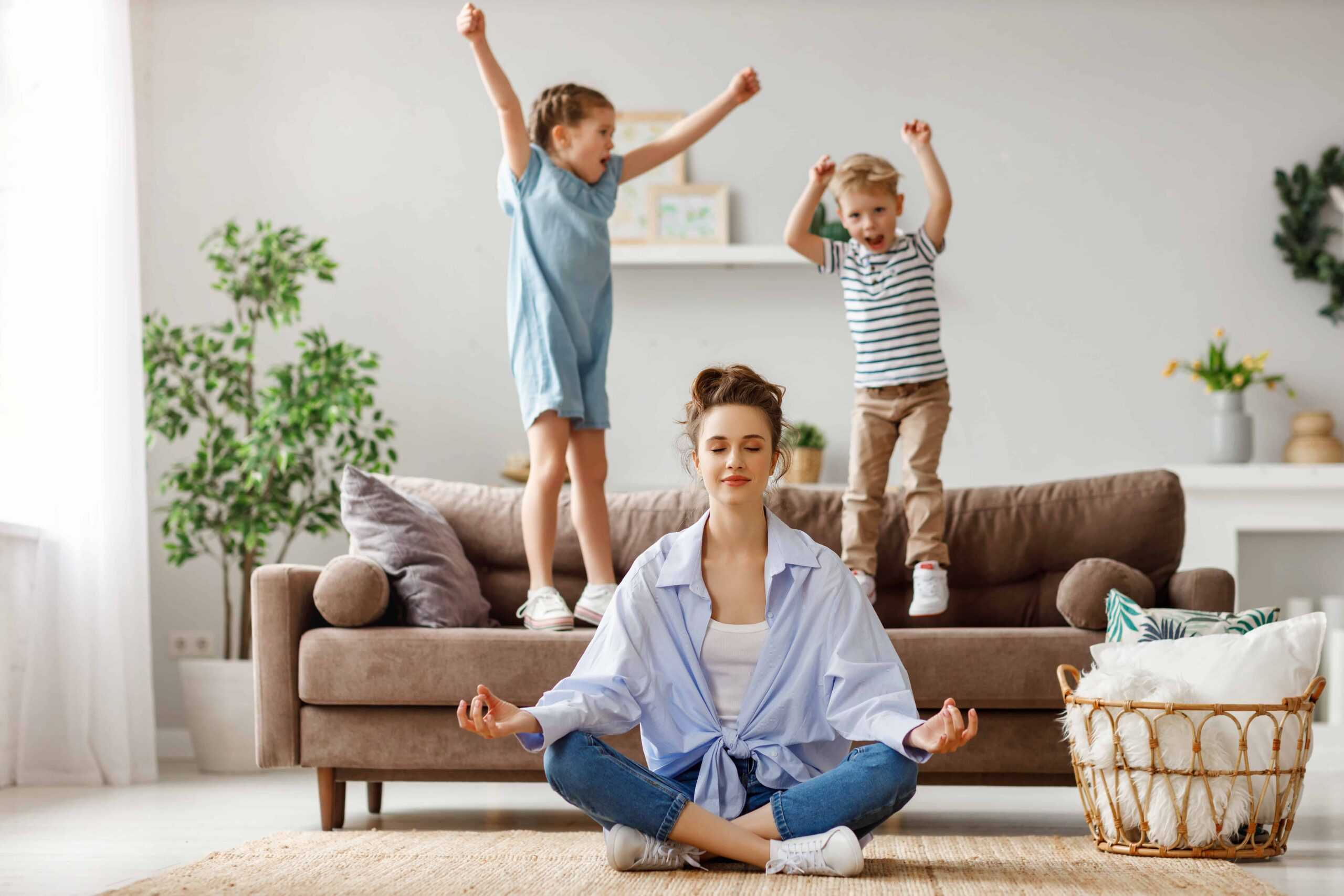Mom meditating while kids jump on the couch